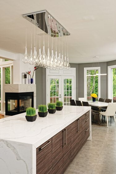 The island features gray-veined quartz countertops with waterfall edges, which contribute to the contemporary vibe.