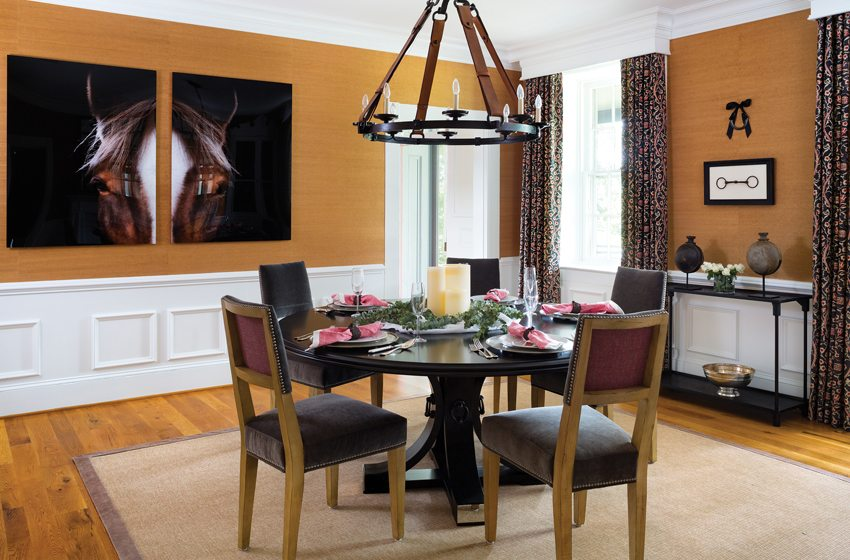 Gold Phillip Jeffries grass cloth contrasts with white wainscot in the dining room.