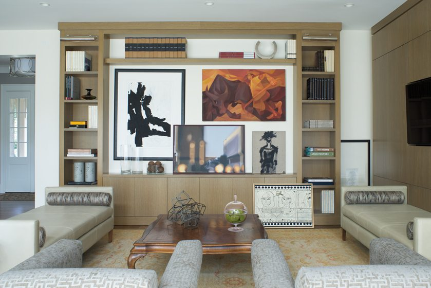 The owners' artwork is showcased in a niche formed by built-in wood shelving in the living room. © John Cole