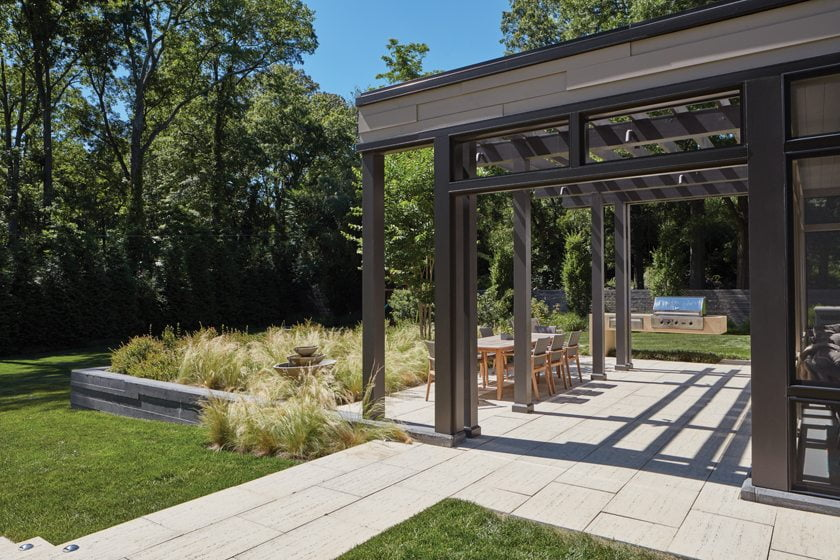 A pergola and dining terrace with a built-in grill are located off the kitchen and enclosed porch. © David Burroughs