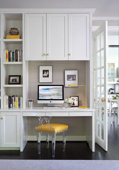 An acrylic Hines & Company chair pulls up to a built-in desk in the family room.