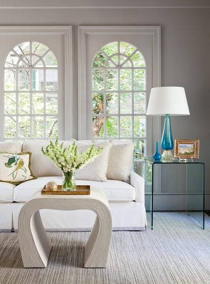 An azure Murano glass table lamp adds a dash of color in the sunroom, where the coffee table is by Thomas O'Brien.