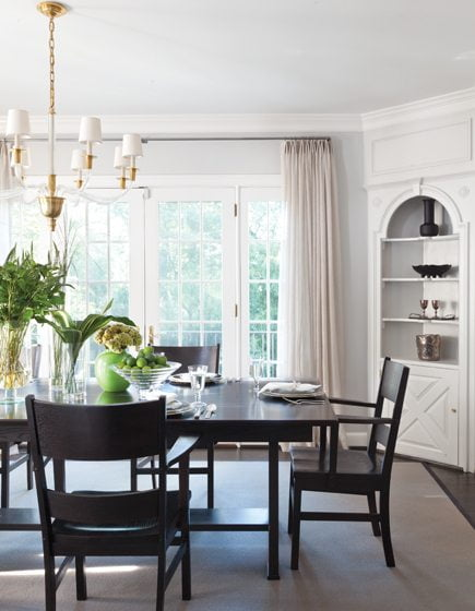 In the dining room, a chandelier from Visual Comfort hangs above the owners' table and chairs.