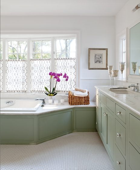 Woodwork in the master bathroom is finished in a soft gray-green, complementing the home's overall color palette.