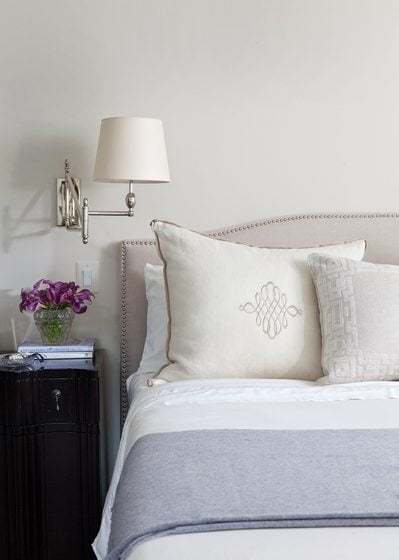 Embroidered bed pillows are illuminated by swing-arm lights from Visual Comfort.