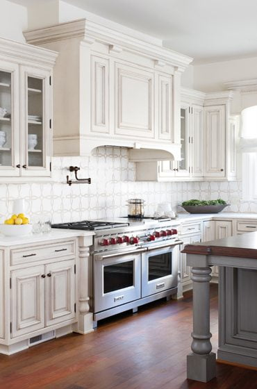 The island and adjacent butler's pantry cabinets are finished in distressed gray.