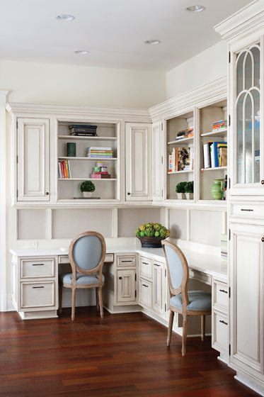 A desk area accommodates two work stations, complete with shelving and linen-covered bulletin boards.