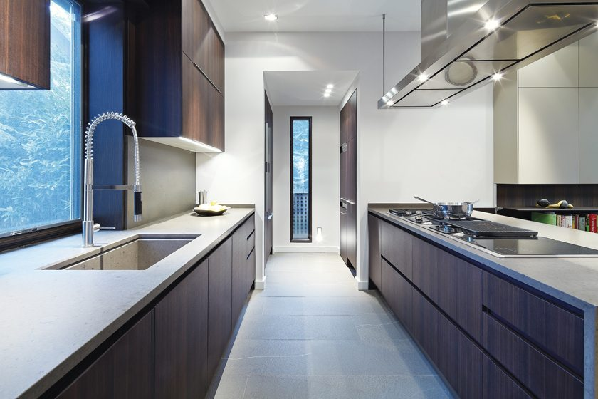 Stone-like ceramic tile floors and carefully planned lighting enhance the spare, minimalist space.
