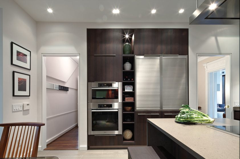 A cabinet wall holds double ovens and two appliance garages—one concealing a coffee center and the other glassware a wine refrigerator.