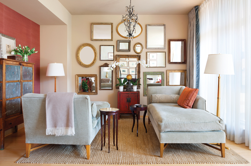 Adjoining the living space, the lounge area showcases a wall of mirrors made with gilt frames.