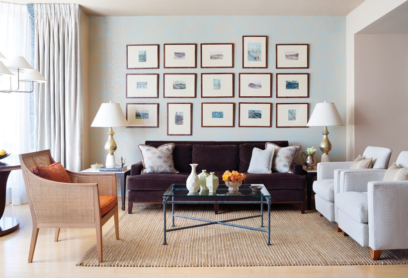 The living room displays a series of watercolor landscapes against a custom-painted damask wall covering.