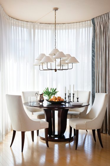 Natural light pours into a niche, furnished with a Baker dining table and chairs by Swaim.