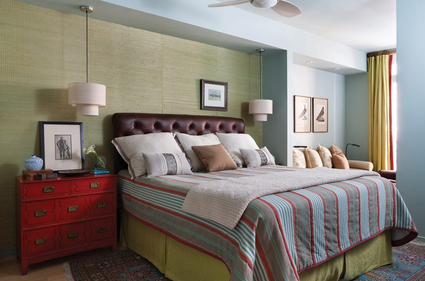 Green raffia wall covering by Phillip Jeffries creates a perfect background for the master bedroom's bright palette.