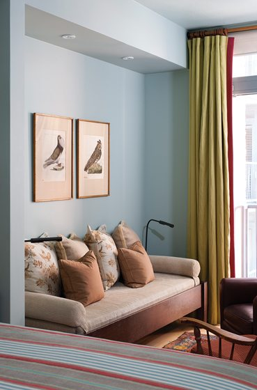 A sitting area contains a settee from Hamilton Furniture, antique prints and linen drapes.