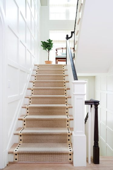 A paneled staircase leads to the second floor.