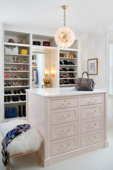 The dressing room houses a faux-fur bench and a glamorous light fixture by Visual Comfort.