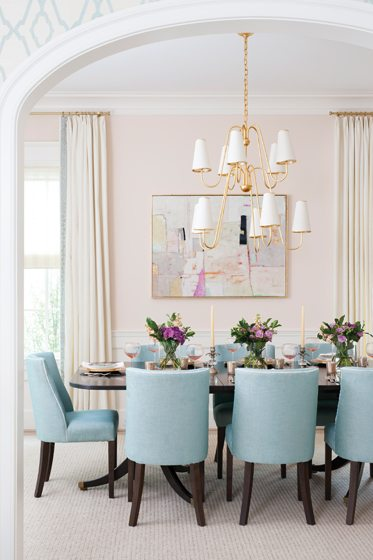 In the dining room, the owners' table is a chic ebony paired with chairs in pale blue fabric by Jane Churchill.