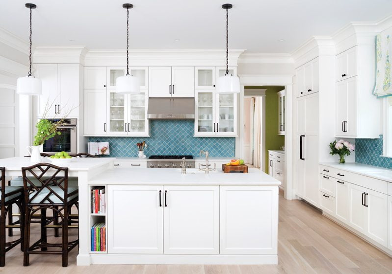 Turquoise backsplash tile by Tabarka Studio adds a burst of color in the crisp, white kitchen.