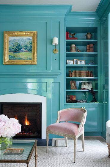Bucking tradition, library paneling is painted in Benjamin Moore's Mill Springs Blue in a high-gloss finish.