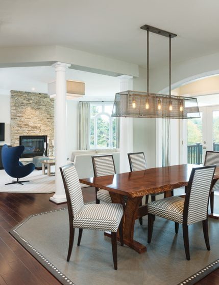 A custom light fixture, a live-edge table and a banded Chilewich rug define the breakfast area.