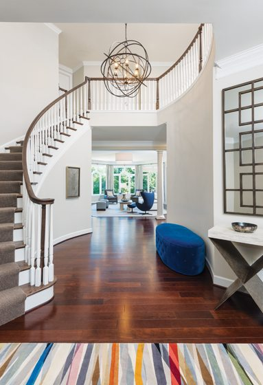 The foyer is furnished with a custom iron-and-stone console and a blue bench.