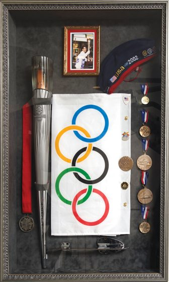 Weiss's home gym displays medals, a skate blade from the 2002 Salt Lake City games and the Olympic torch he carried through Alexandria.