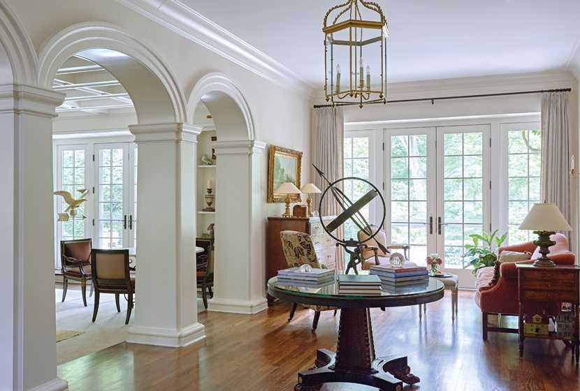 A wide, welcoming foyer is furnished with antiques; it overlooks a lush back garden through French doors.