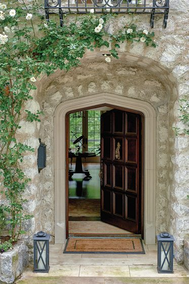 Visitors enter the stone manor house through a peaked, Tudor-style doorway.