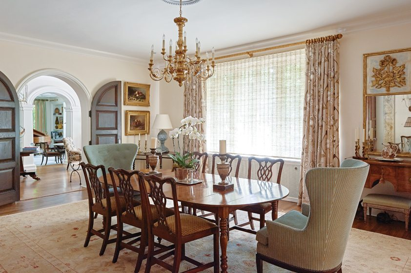 Wide, arched double doors separate the entry hall from the elegant dining room.