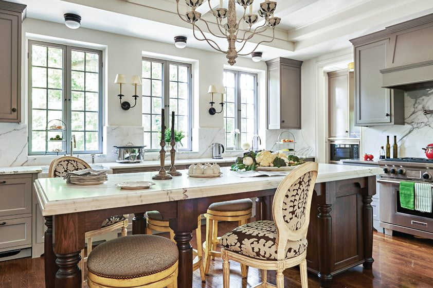 The kitchen features clean-lined cabinetry, a Niermann Weeks chandelier and stools from Interior Concepts.