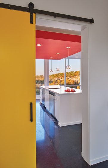 A bright-yellow sliding barn door separates the guest bedroom from the kitchen .
