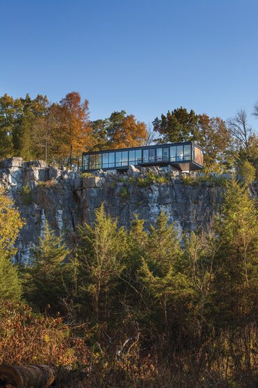 The house perches at the edge of a 90-foot cliff.