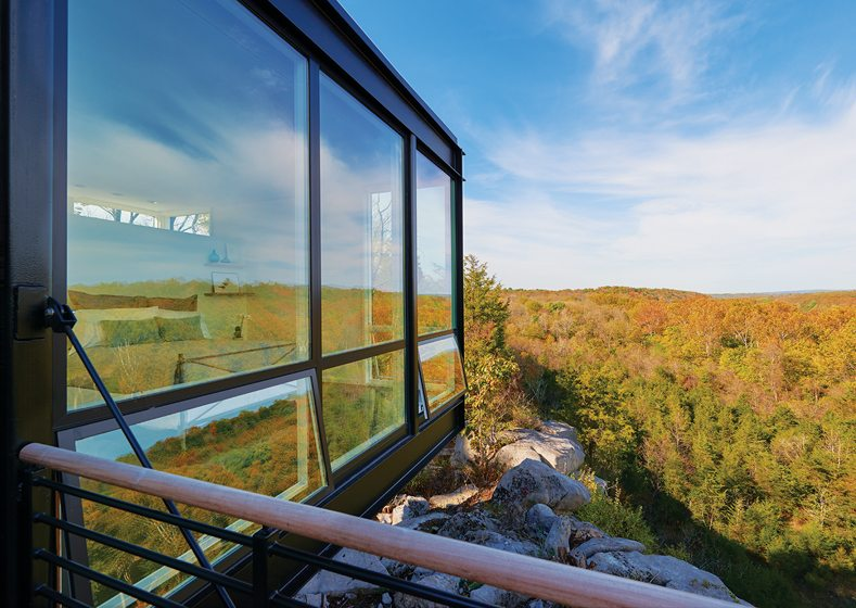 A view from the back balcony reveals the master bedroom wing, which cantilevers above rocky terrain.