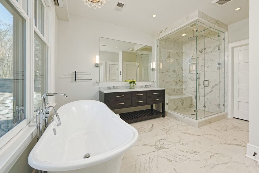 The spacious master bath is outfitted with a Victoria & Albert standing tub and a custom glass shower.