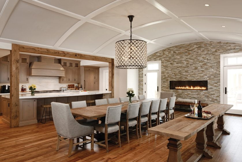 Rustic elements combine with a quartzite-tile fireplace wall in the barrel-vaulted dining room.
