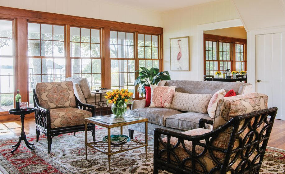 Rattan armchairs from Lexington Home and a Kravet sofa gather around a sturdy coffee table from Worlds Away.