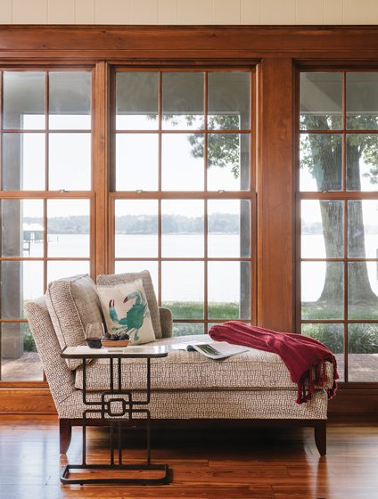 A chaise and a stone-topped table from Gabby Home stand at the window.