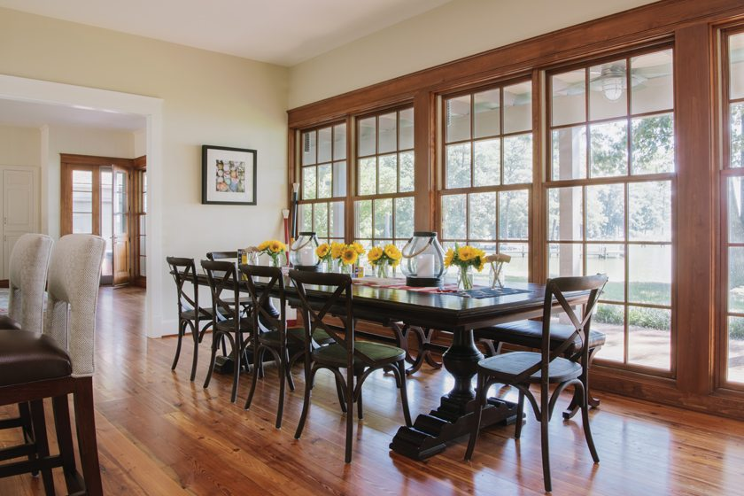 A Chaddock trestle table is paired with low-backed dining chairs and benches so as not to impede the view.