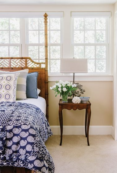 In the master bedroom, a rattan bedstead from Lexington Home imparts the feel of a holiday abode.