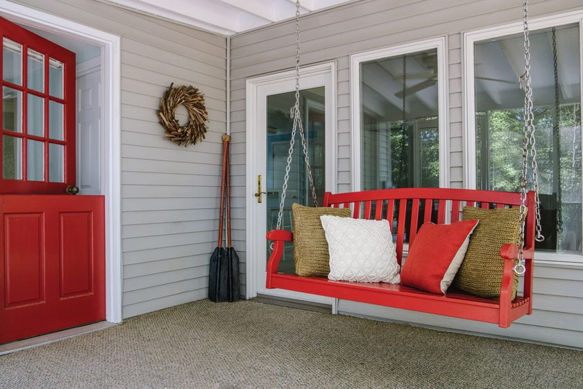 The guest cottage porch boasts a swing from Grandin Road.