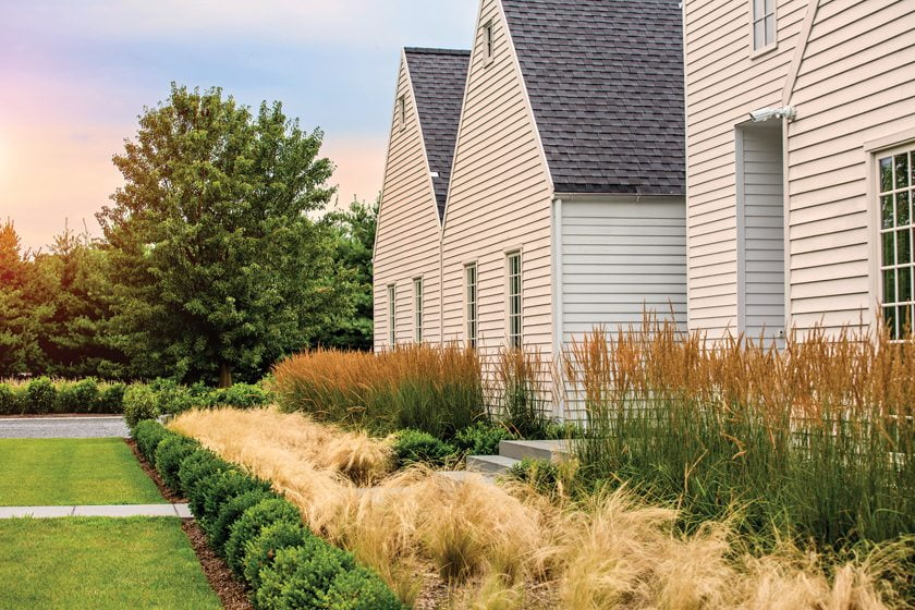 Bands of boxwood, Karl Foerster grass and nassella soften the home's stark, white façade.