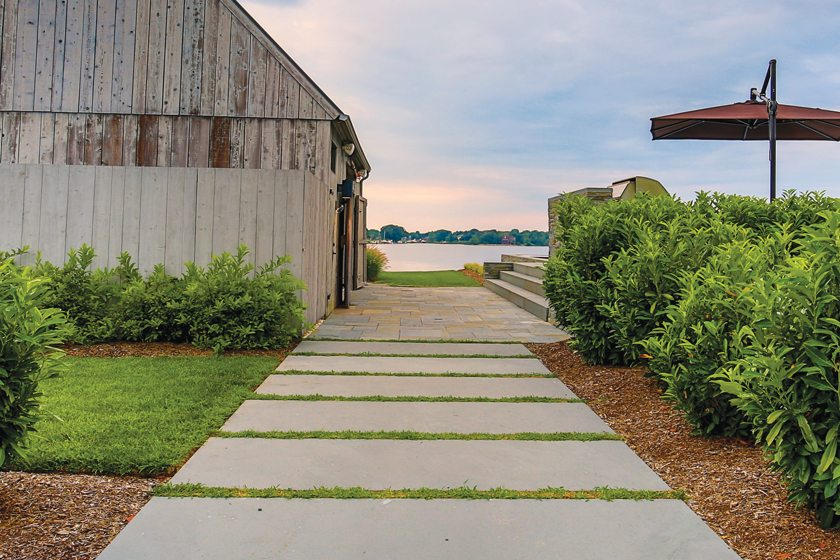 A flagstone path lined with cherry laurel leads to the pool and guest house.