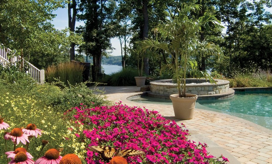 A pool scape designed and installed by Walnut Hill boasts a scenic river view. © Jay Stearns