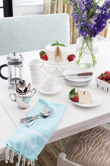The existing breakfast table, painted white, holds a tempting buffet of coffee and cake.
