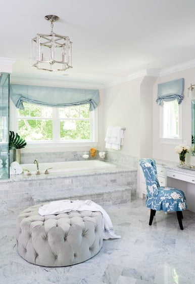 The master bath is clad in Carrara marble with a plush ottoman from Pottery Barn Kids.