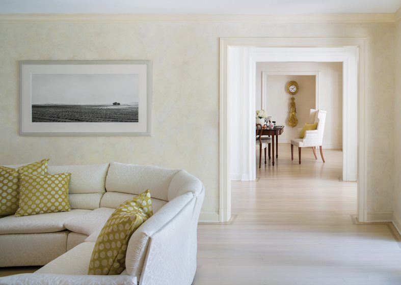 The dining room is visible beyond the living room, with its soft, monochromatic color scheme.