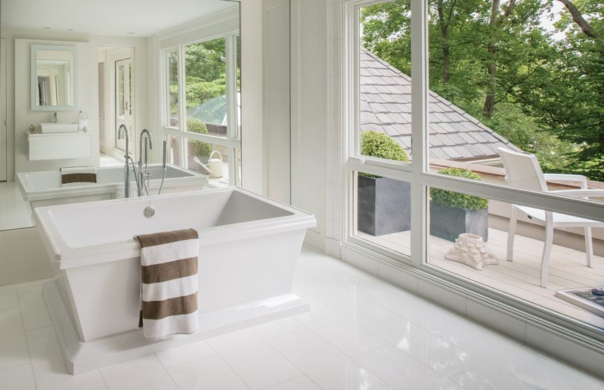 A soaking tub overlooks the terrace in the bright, airy bathroom.