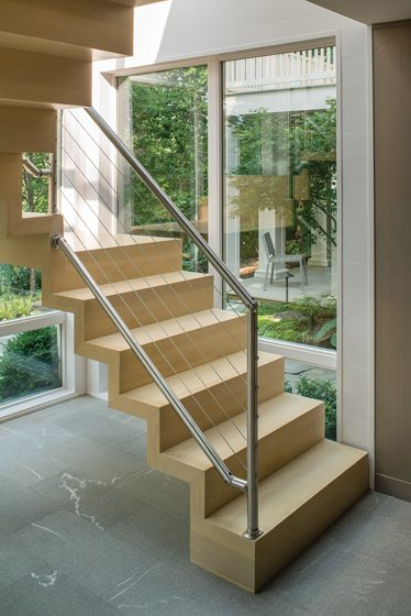 The sculptural staircase combines laminated-oak treads and stainless-steel railings.