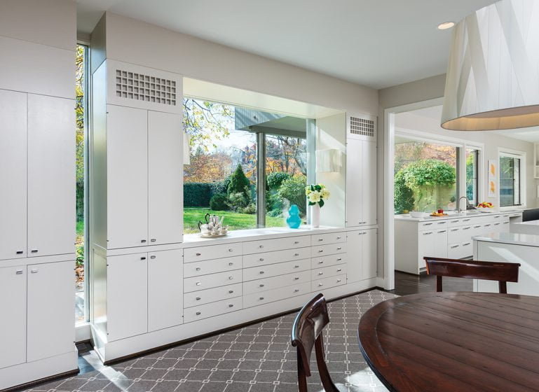 The dining room complements the kitchen with freshly painted cabinetry and a picture window.