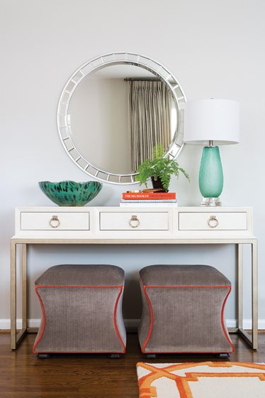A faux embossed-leather console and a Currey & Company lamp grace the entry.